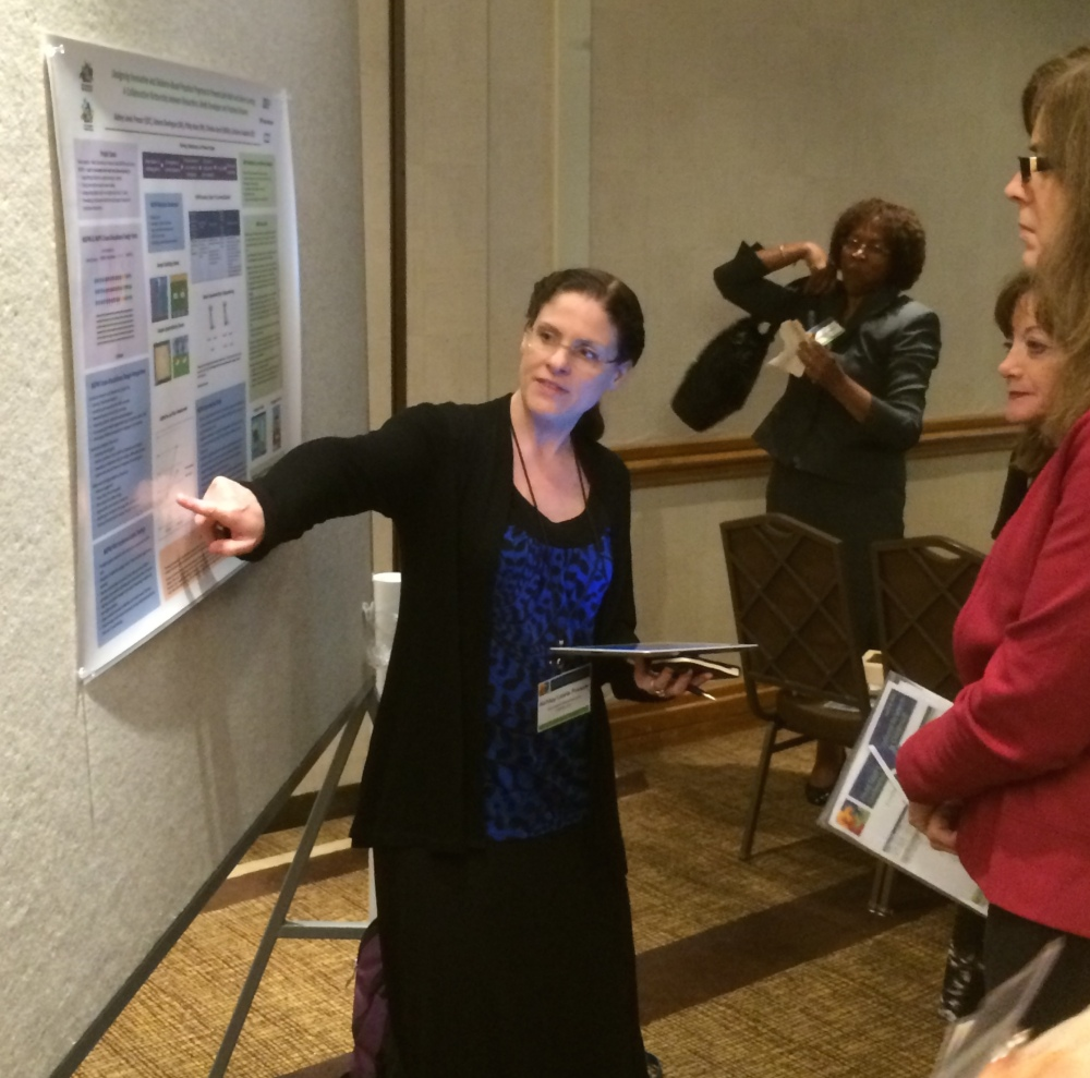 Ashley Lewis-Presser talking with conference attendees about NGPM.